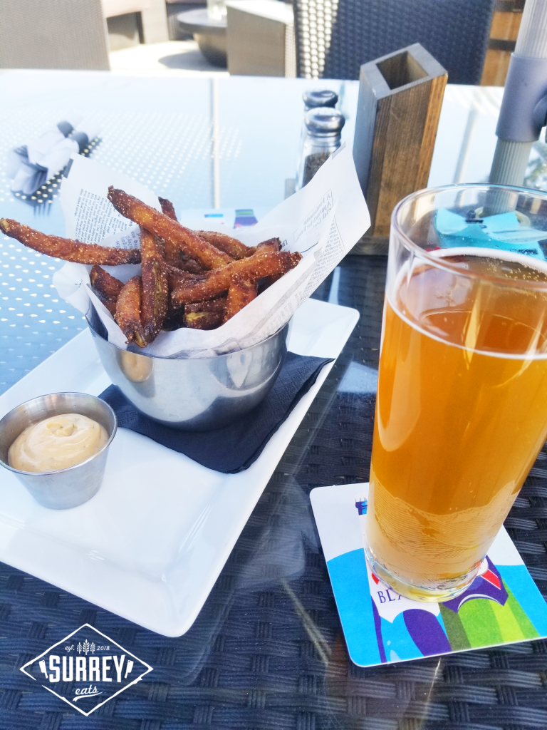 Glass of beer and pickle fries on patio table