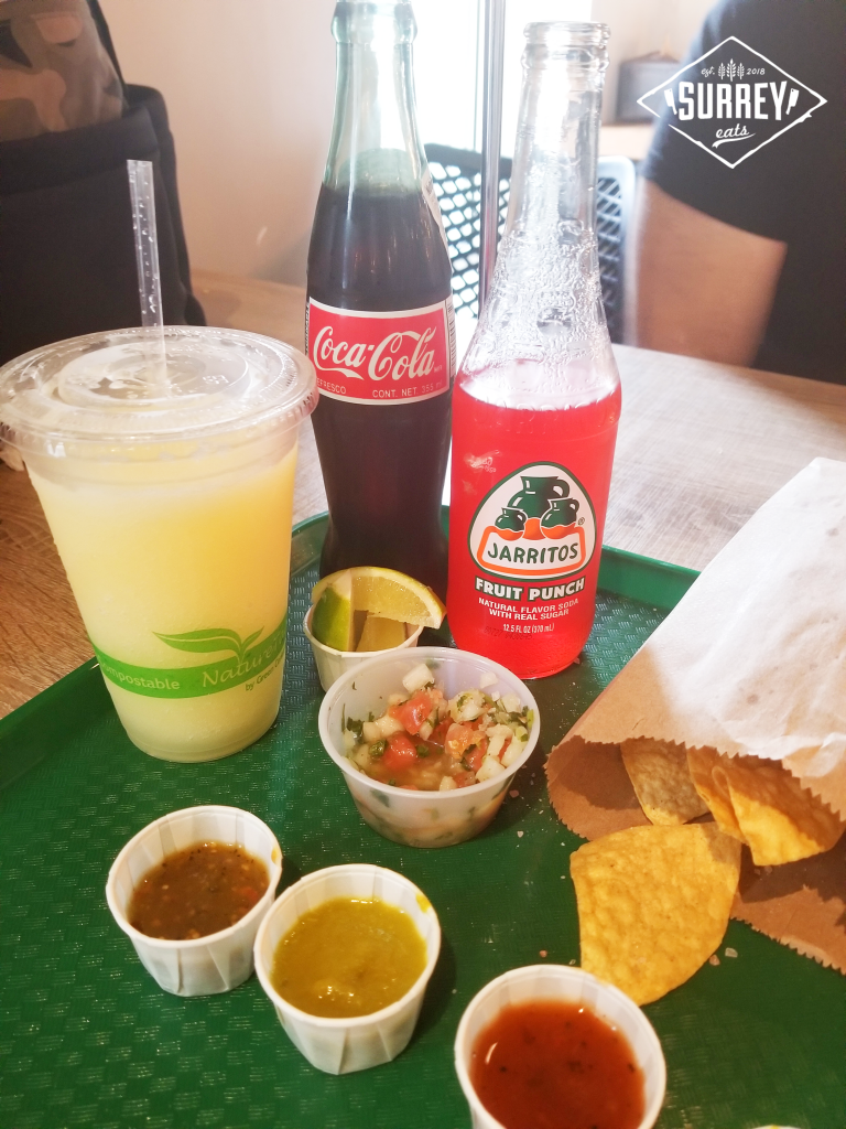 Drinks including lime margarita, chips, salsa and hot sauces