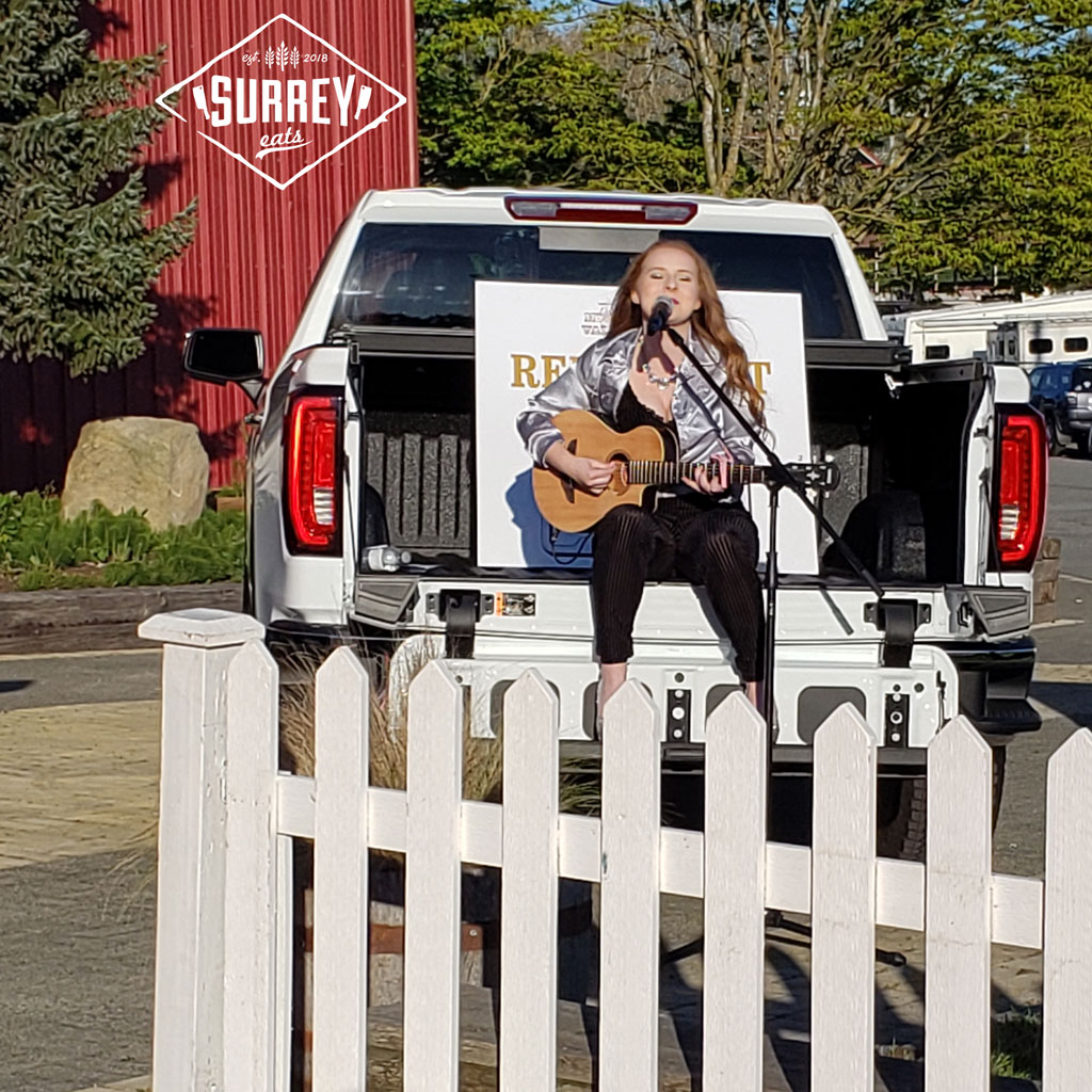 Girl singing country music and strumming a guitar on the back of a pickup truck