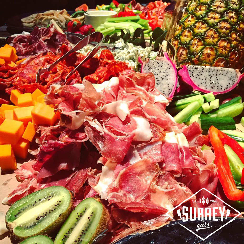 Thinly sliced prosciutto surrounded by fruits, vegetables and cheese