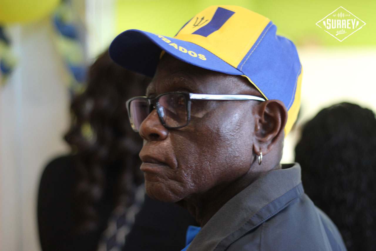 An older gentleman wearing a Barbados hat