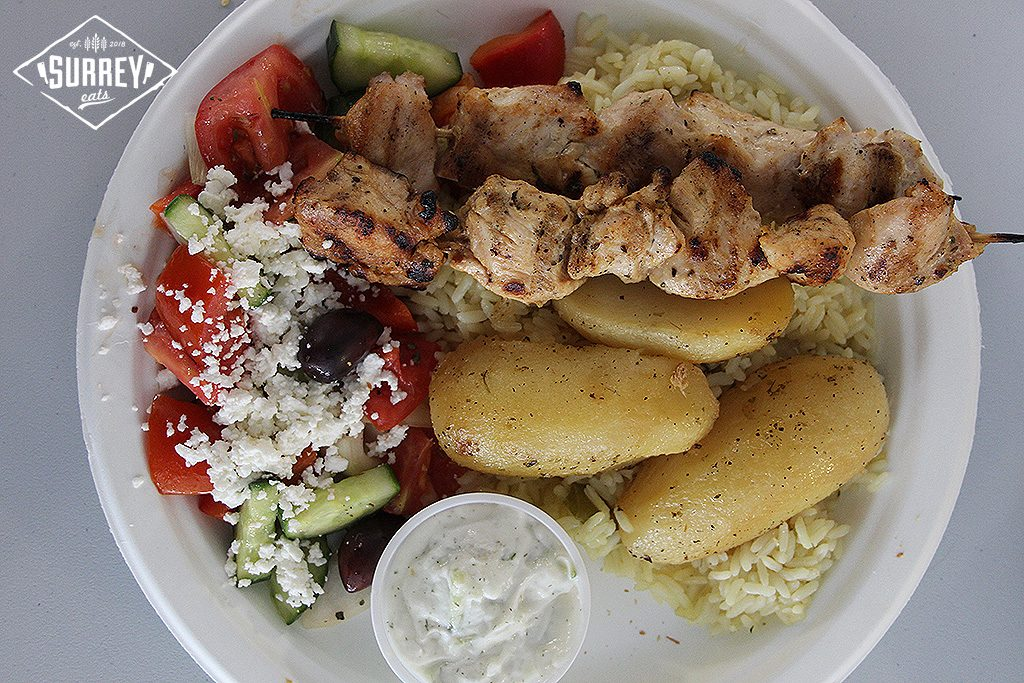 A chicken souvlaki dinner with roast potatoes, rice pilaf, greek salad, and tzatziki