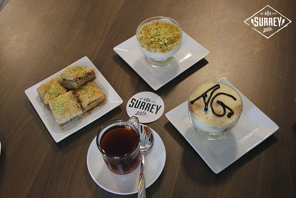 A diamond-shaped arrangement of plates with three desserts and a cup of tea. The desserts are baklava, custard, and tiramisu, and there's a Surrey Eats sticker in the center of the arrangement.