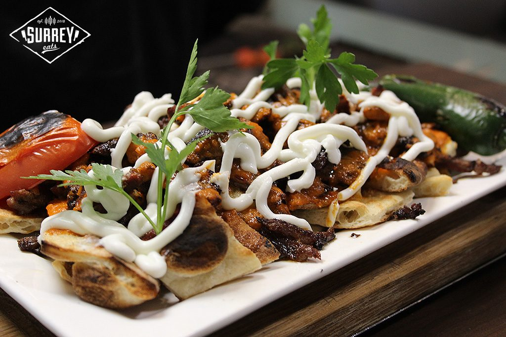 Iskender kebab, shavings of donair beef on pieces of naan and covered in yogurt