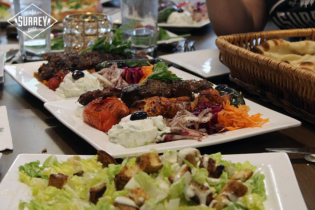 Two shish kebab platters with Caesar salad in the foreground