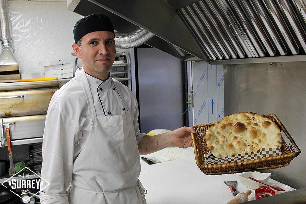 A man holding naan in a basket