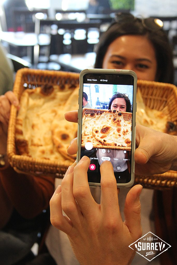 Someone snaps a picture on their phone of a food blogger holding a basket of naan