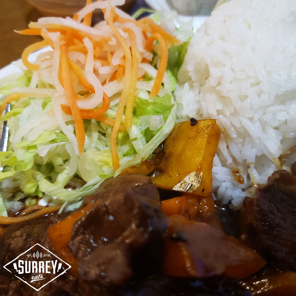 Shaken stir fried beef close up with rice and salad.  There is a sticker on one of the peppers.