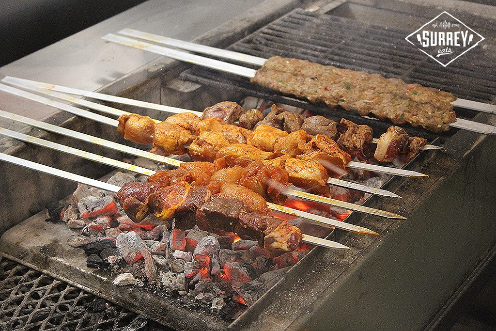 Skewers of meat cooking over coals