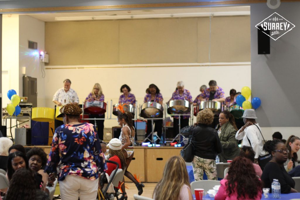 Inside the Taste of Barbados festival in Surrey, BC, steel drums are played on stage while festival-goers mingle at tables below