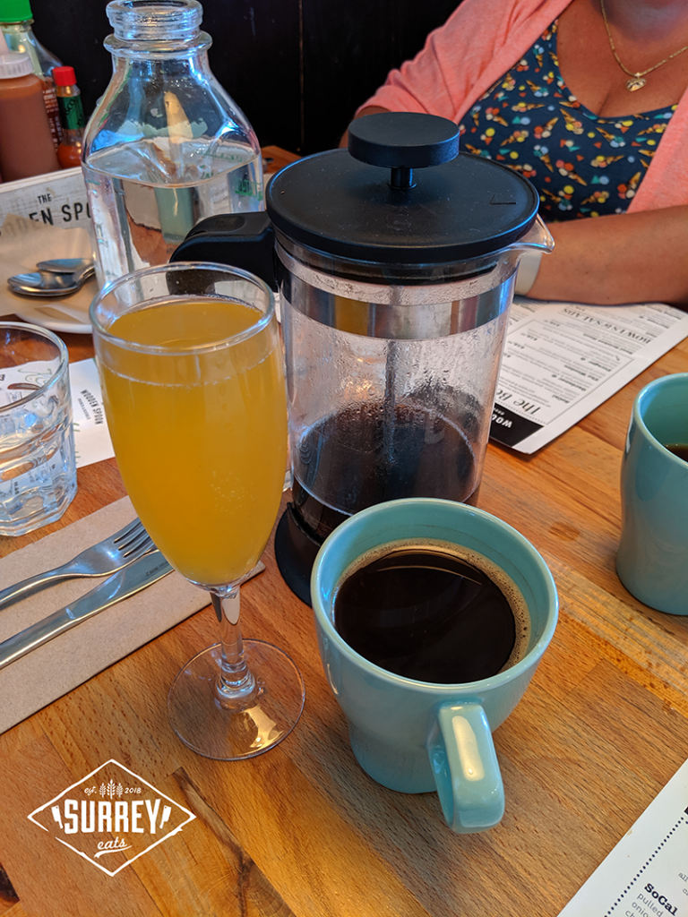 Pear-peach mimosa cocktail and French Pressed coffee on table at Wooden Spoon restaurant