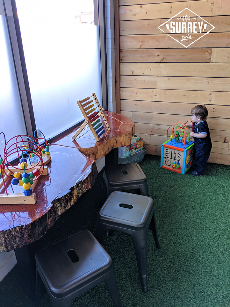 Child playing in toy area at the Wooden Spoon
