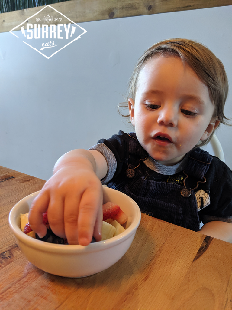 Toddler reaching for fruit salad