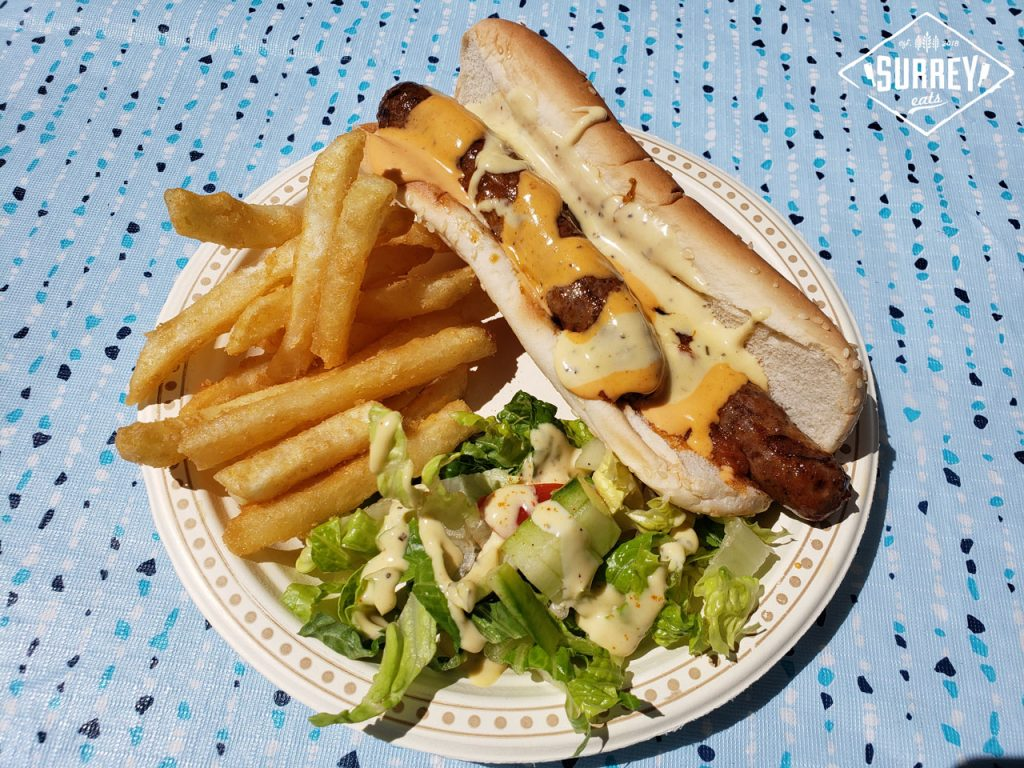 A merguez hot dog covered in sauces with a side of fries and a side salad. It's on a paper plate set on a blue patterned tablecloth. Photo taken at Surrey Fusion Festival.