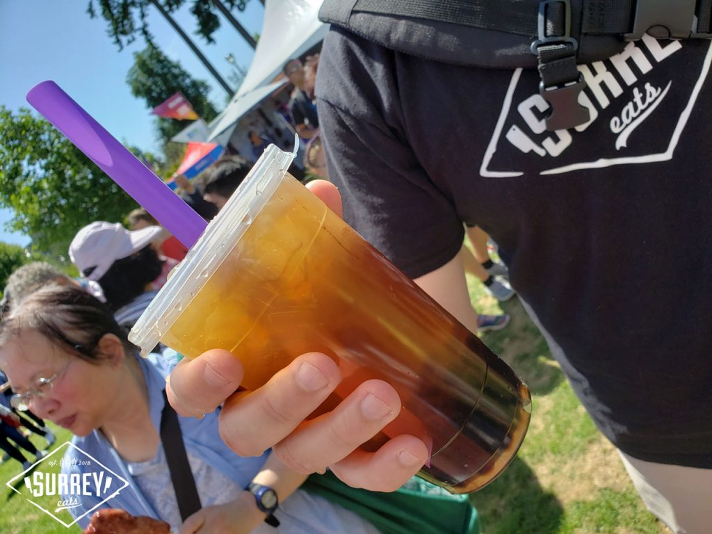 Craig from Surrey Eats holding a black tea with pearls. It has a purple straw.