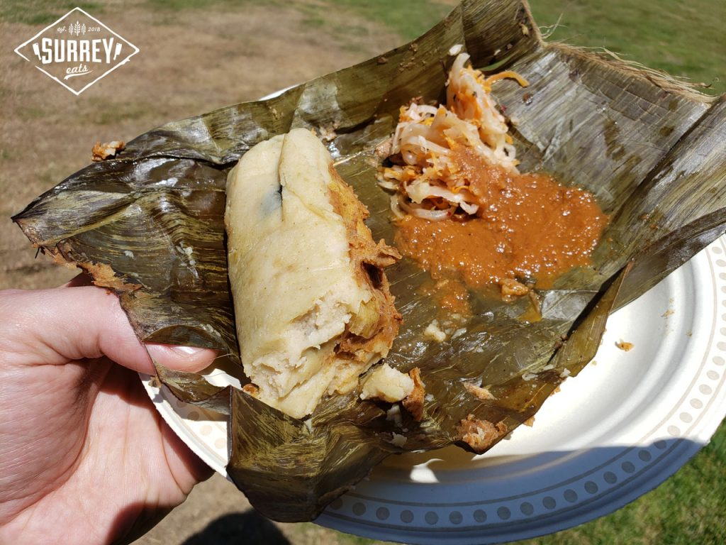 A chicken tamale served on a banana leaf with hotsauce and cabbage salad