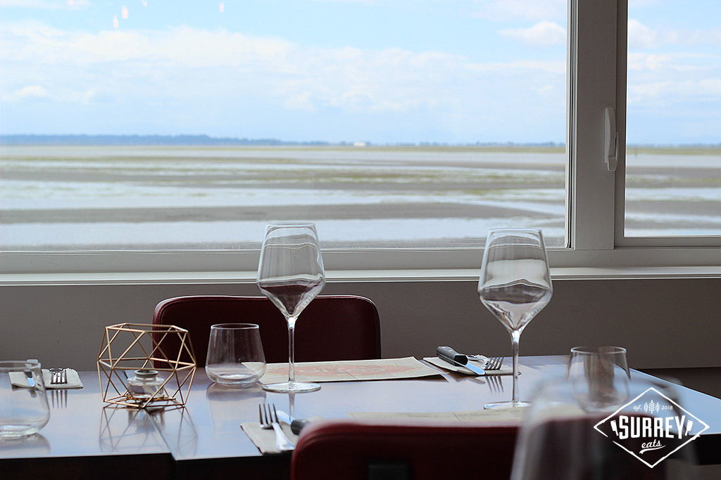 Two wine glasses on a table with a Surrey beach view through the window