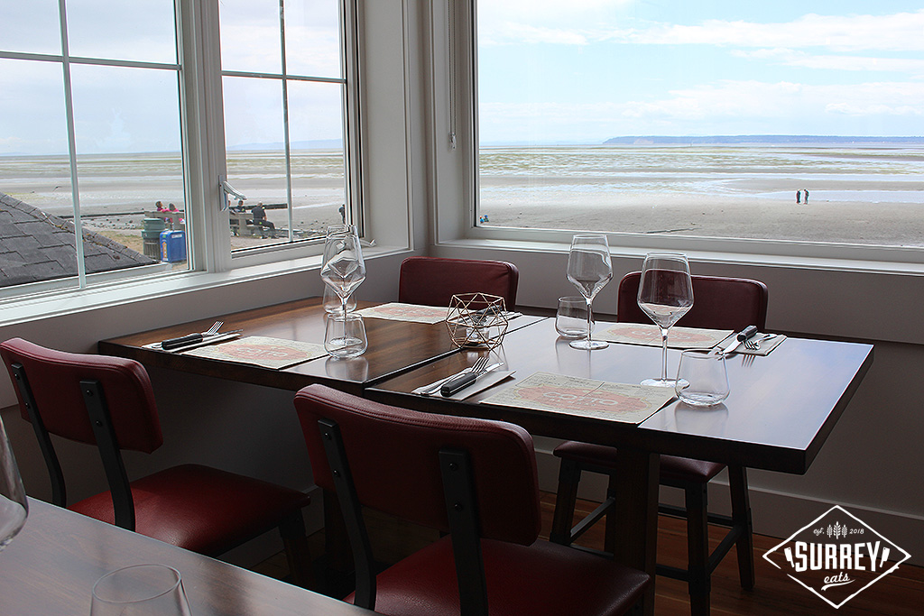 A view of Crescent Beach through a window at Cotto al Mare restaurant with a table in the foreground