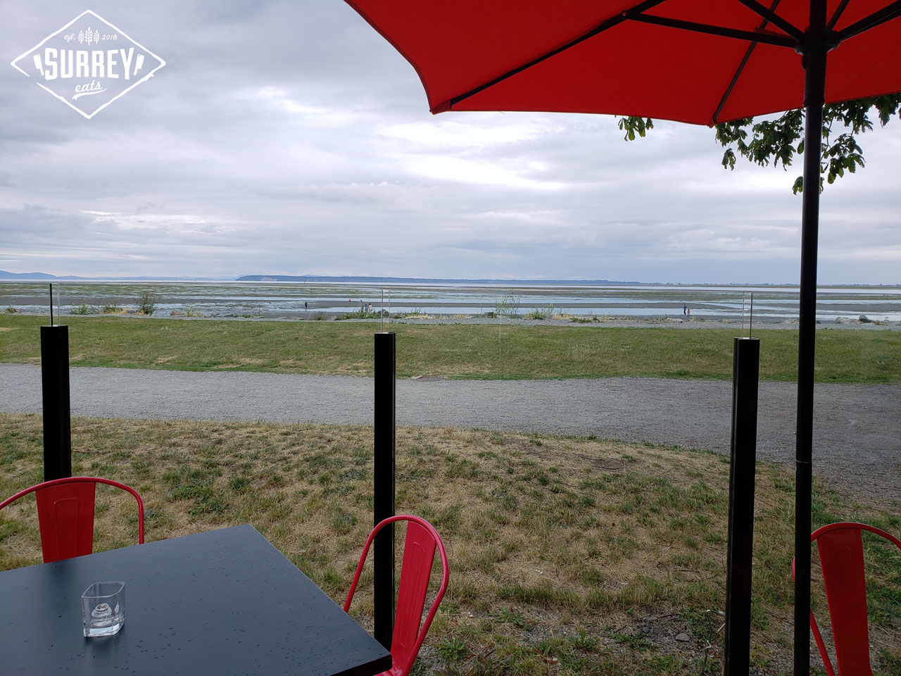 The view of Crescent Beach from under a patio umbrella at Cotto al Mare restaurant