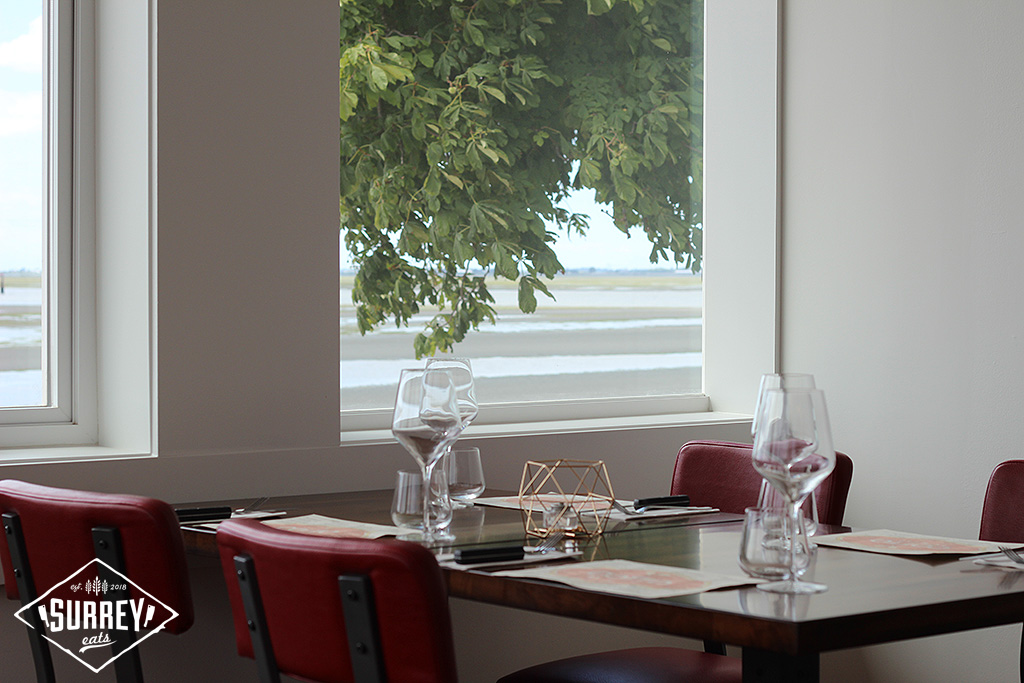 A tree is seen through a window behind a table at Cotto al Mare
