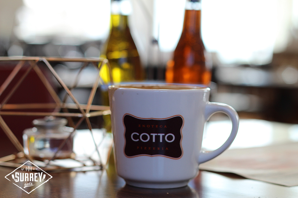 A coffee mug emblazened with the Cotto logo and two types of olive oil in the background
