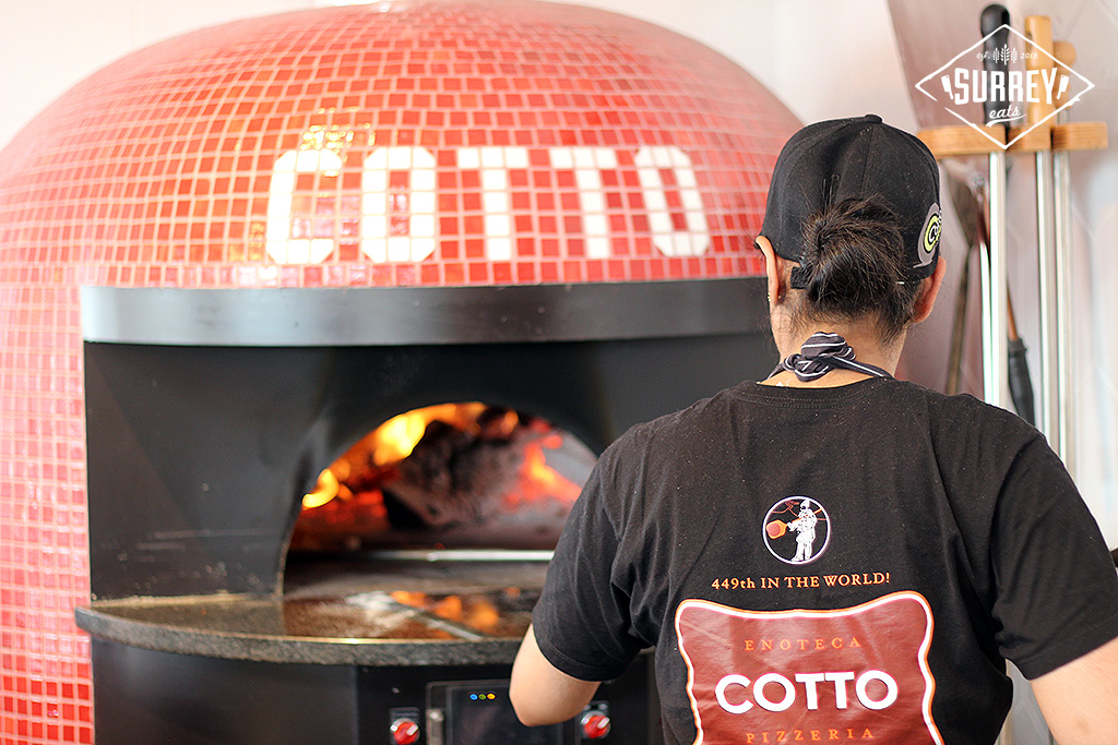 A woman in a Cotto shirt making pizza at a pizza oven with Cotto written on it