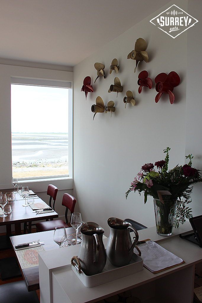 Tables, flowers, and wall decorations inside Cotto al Mare restaurant