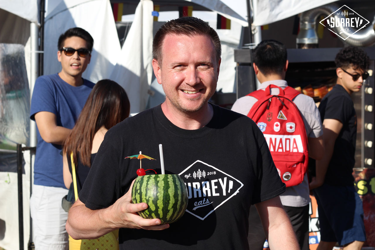 Craig from Surrey Eats holds up a whole melon drink while wearing a Surrey Eats shirt