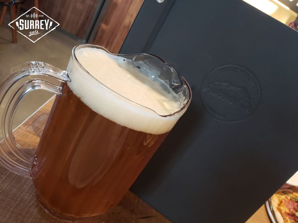 A pitcher of Four Winds beer with a Rocky Mountain Flatbread menu propped up behind it