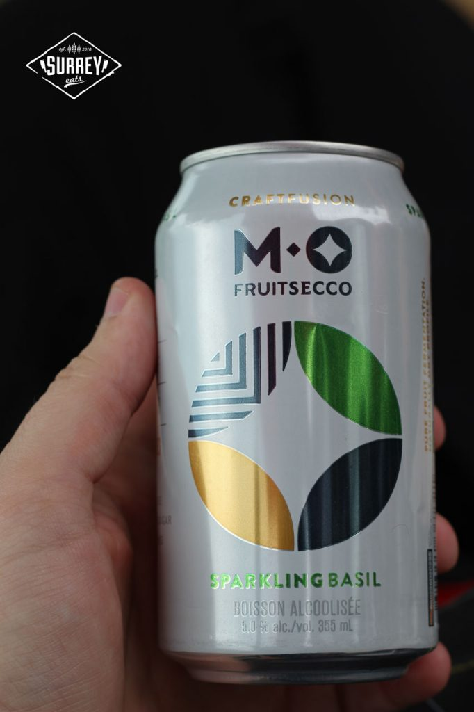 Craig's hand holding a can of M.O Fruitsecco Sparkling Basil flavour