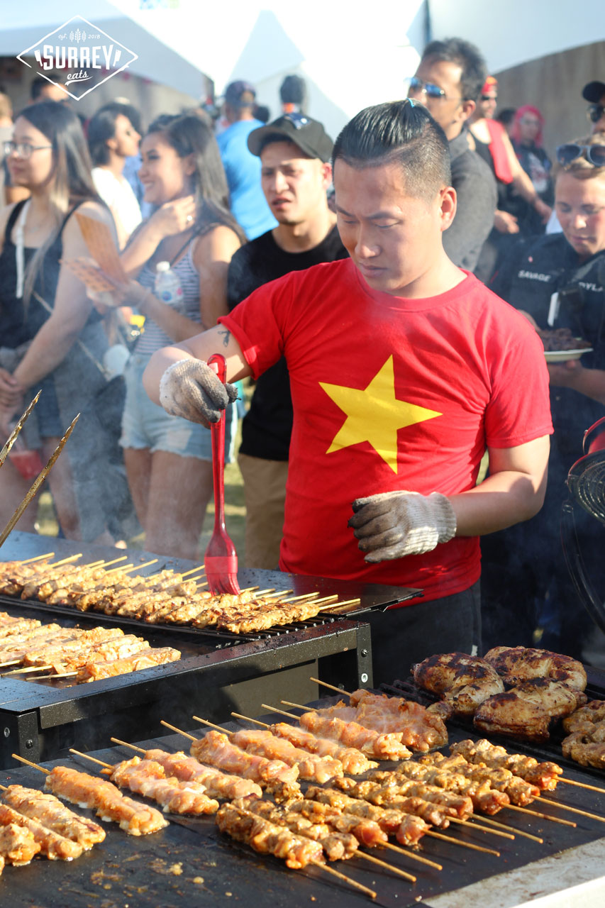 An Asian man brushing sauce on barbecue skewers at Fusion Fest
