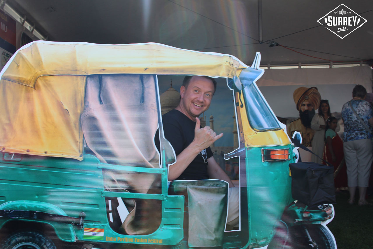 Craig from Surrey Eats sits in a cardboard Indian tuk tuk cutout