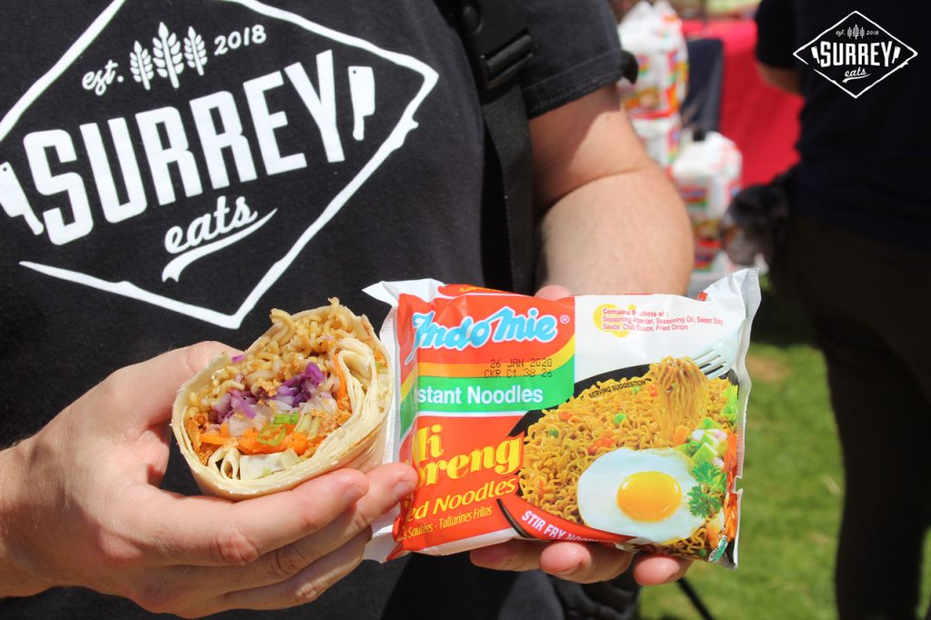 Craig from Surrey Eats holds up half an Indo Mie Noodle Burrito and a package of Indo Mie Mi Goreng instant noodles