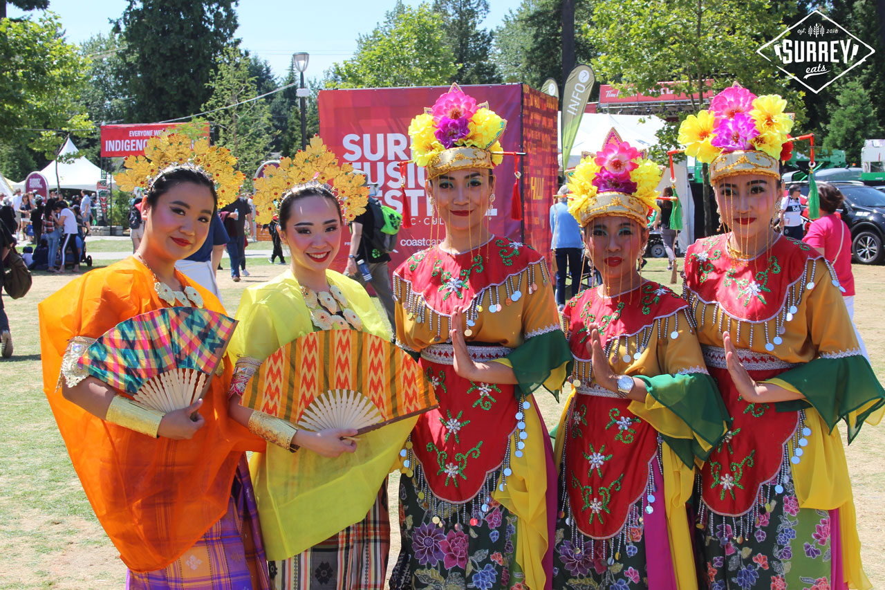 Traditional dancers from Indonesia holding fans and wearing brightly coloured outfits
