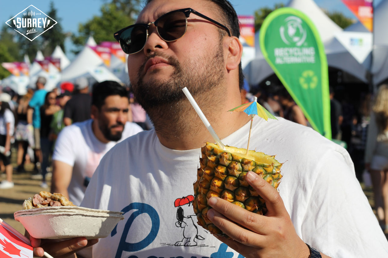 James from Surrey Eats holding a whole pineapple drink