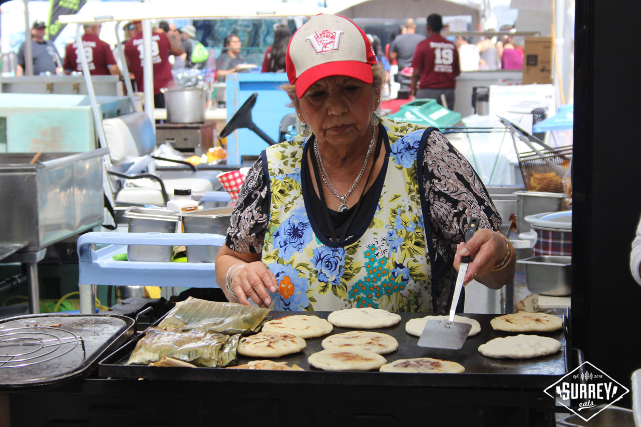 An elderly woman cooks pupusas and tamales at Surrey's Fusion Fest