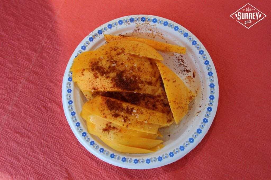 A top-down shot of a plate of mangos covered with salt and chili powder on a red tablecloth at Fusion Festival