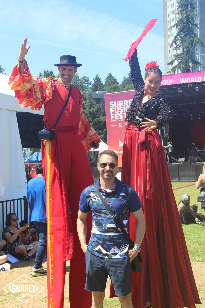 Matt from Surrey Eats stands with two stilt walkers at Fusion