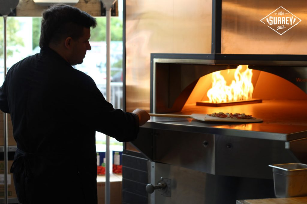 A man puts a flatbread pizza into Rocky Mountain Flatbread Surrey location's pizza oven
