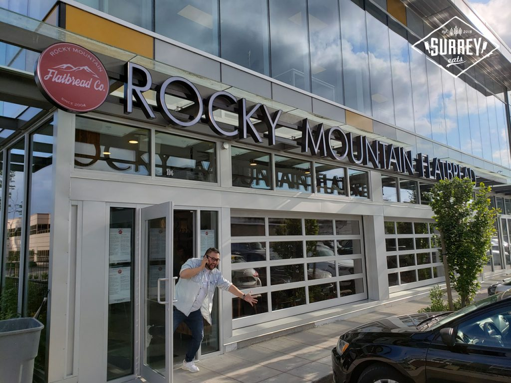 The exterior of Rocky Mountain Flatbread's Surrey location with James from Surrey Eats waving from the door