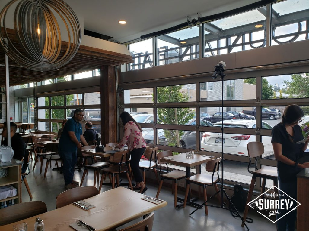 The interior of Rocky Mountain Flatbread's Surrey location with a shot of the garage-style doors