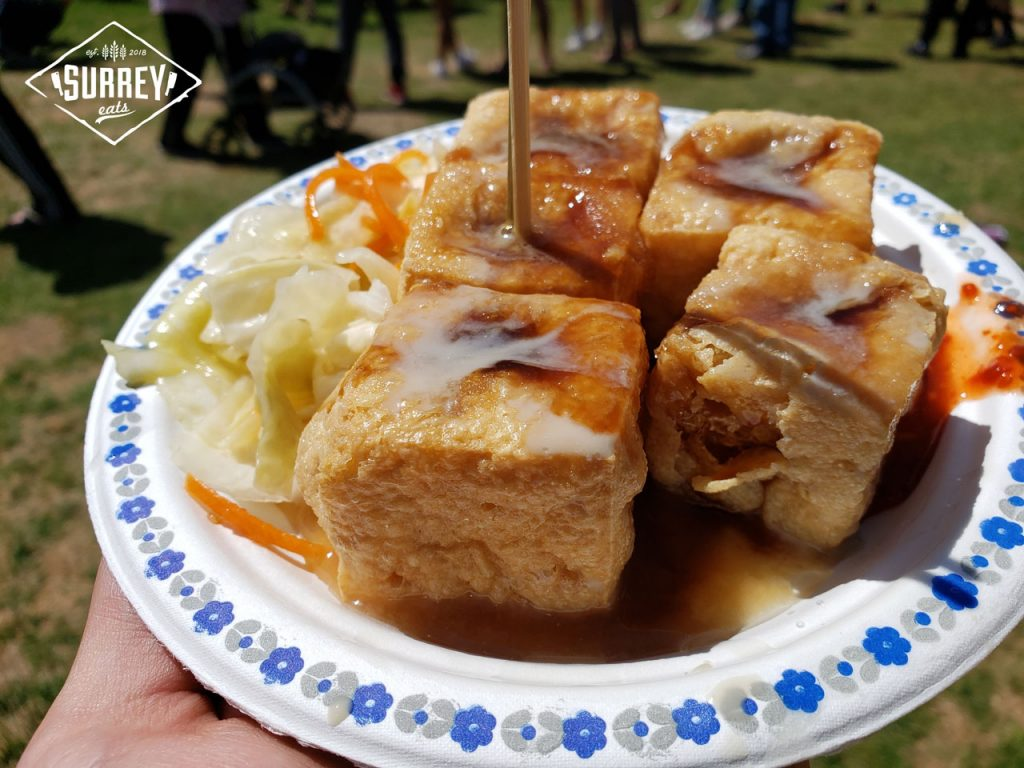 5 pieces of deep fried stinky tofu with hotsauce and pickled cabbage on a plate at Surrey Fusion Festival
