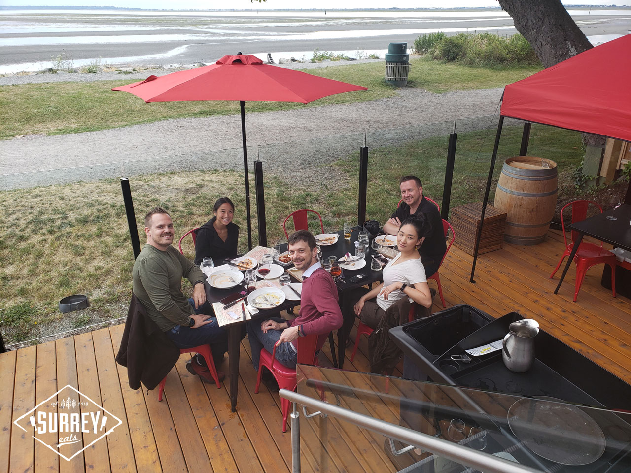 Craig and Michelle from Surrey Eats seated with three friends on Cotto al Mare's patio