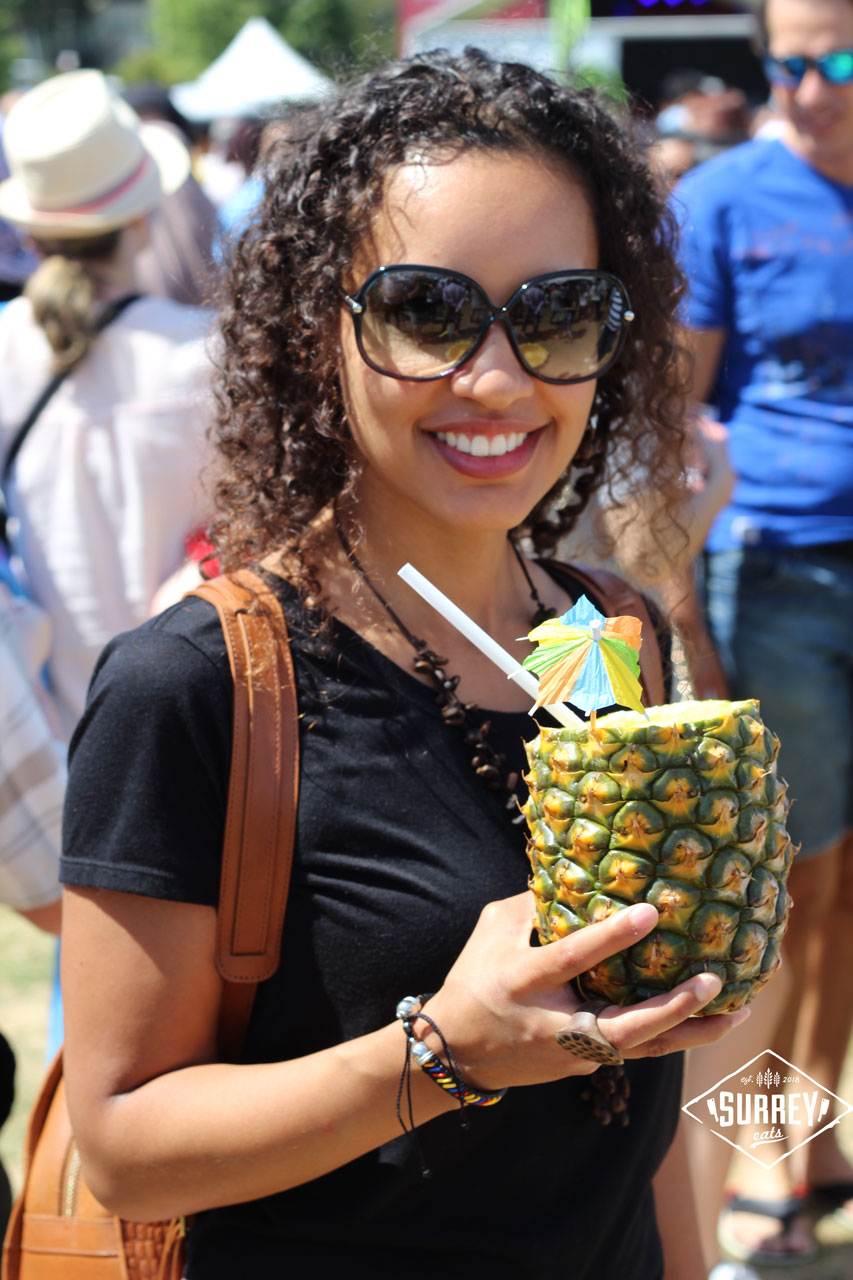 A smiling woman holds a whole pineapple drink with an umbrella in it