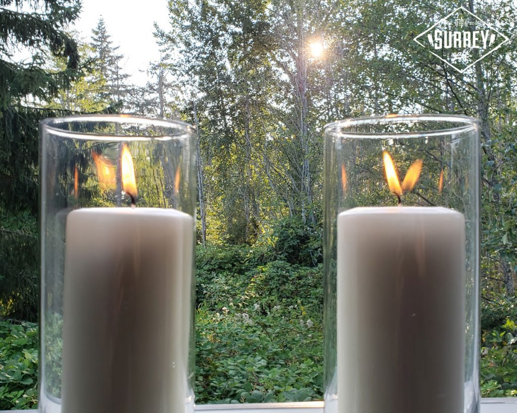 Candles burning in a window at Black Market Supper Club's secret location in Surrey. A sun sets in the forest in the background.