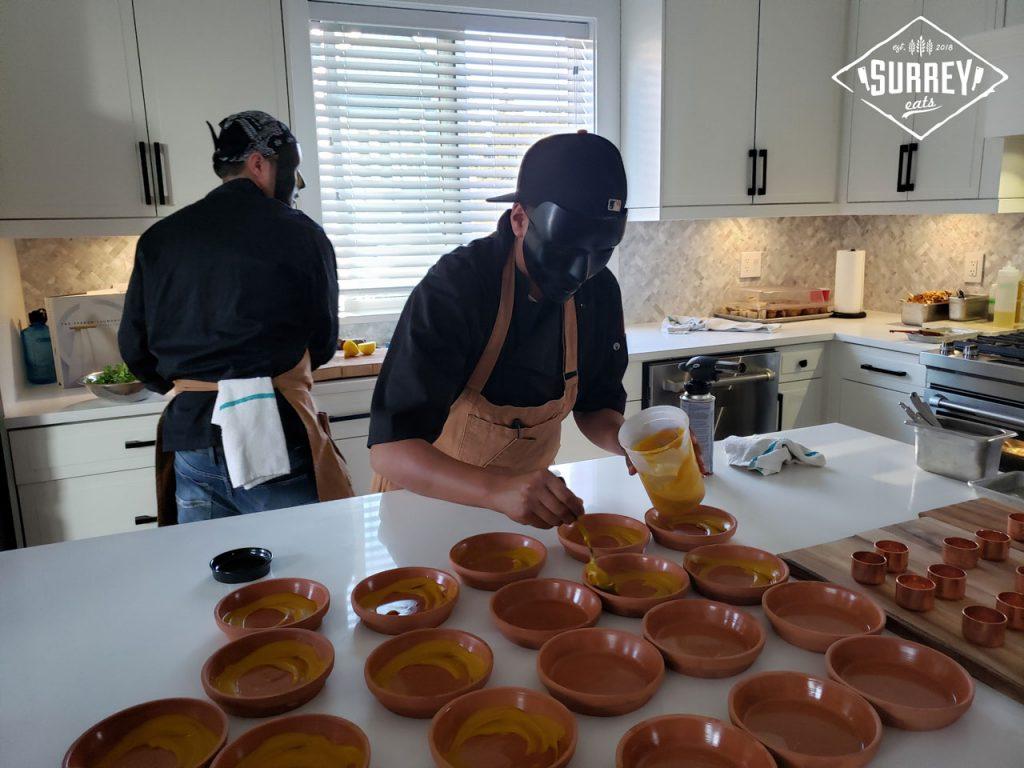 Chefs preparing their lobster pancake dish.