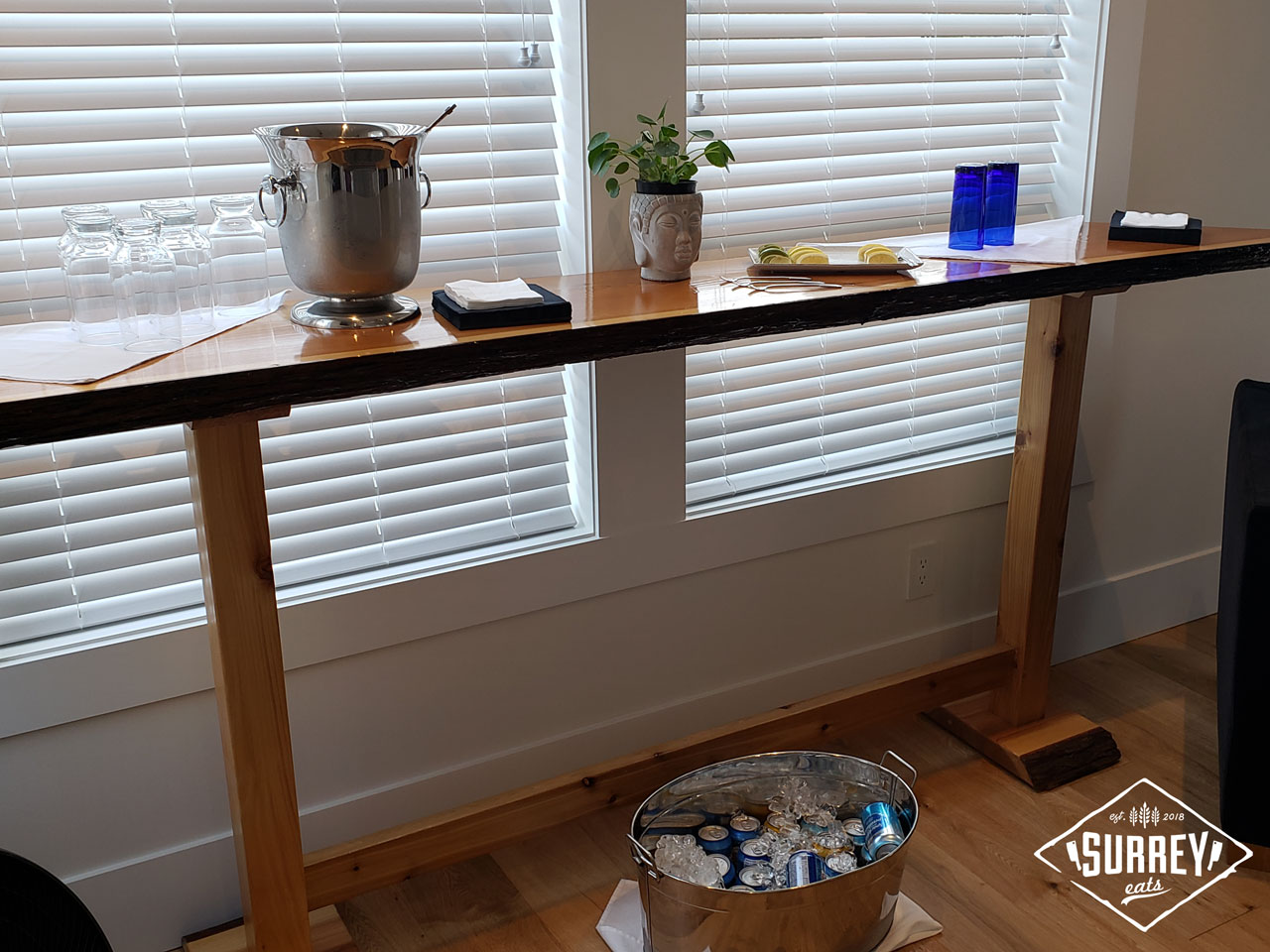 Free mixers in an ice bucket and a shelf with glasses, a plant, and lemons and limes