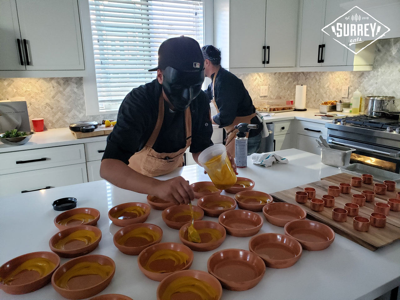 Black Market Supper Club chefs spreading carrot puree into bowls
