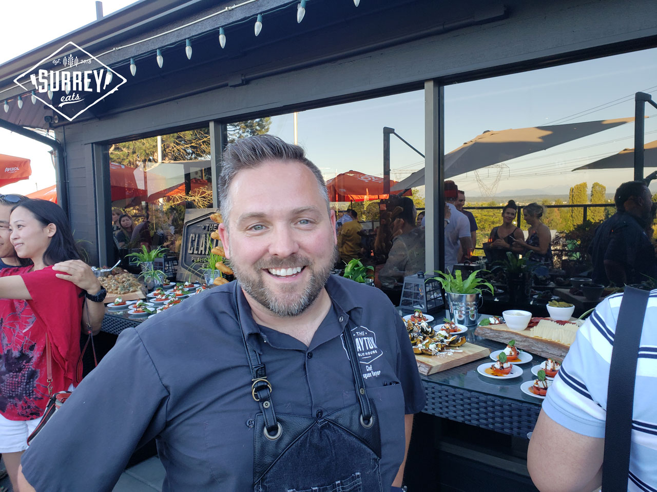 Chef Hugues Voyer from the Clayton Public House smiles in front of his food spread for Surrey Eats Summer Social