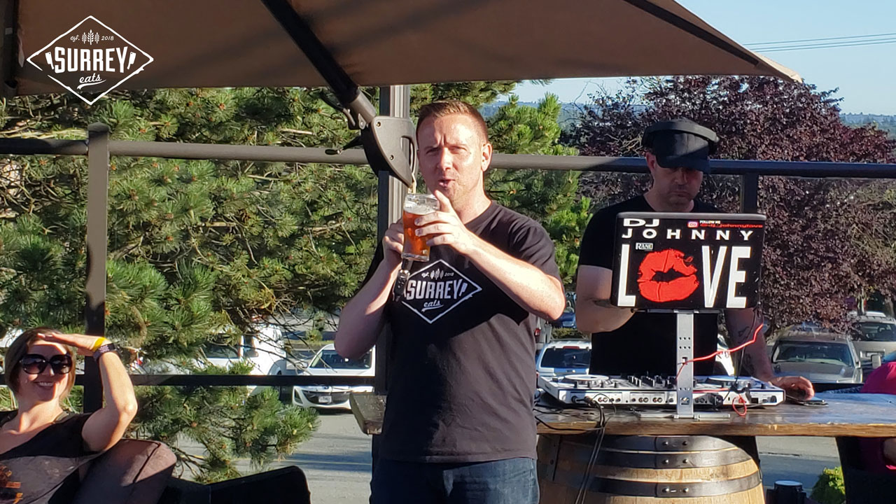 Craig from Surrey Eats addresses the crowd at Surrey Eats Summer Social while holding a beer and pointing